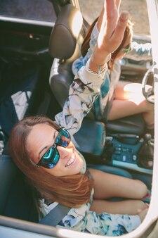 Bovenaanzicht van gelukkige jonge vrouwenvrienden met zonnebril die plezier hebben in de auto in een roadtrip-avontuur. vrouwelijke vriendschap en vrije tijd concept.
