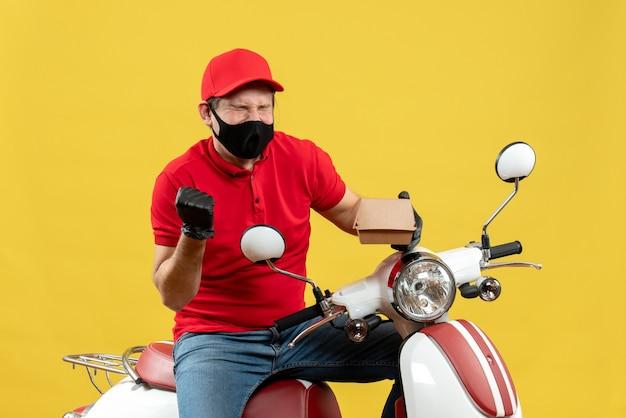 Bovenaanzicht van gelukkige trotse bezorger die uniform draagt en hoed handschoenen in medische masker zittend op scooter met volgorde