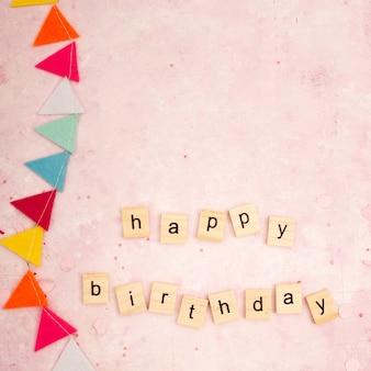 Bovenaanzicht van gelukkige verjaardagswens in houten letters met slinger