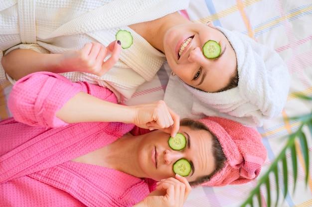 Bovenaanzicht van gelukkige vrouwen met plakjes komkommer op ogen