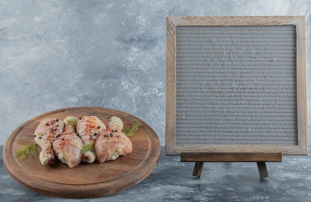 Bovenaanzicht van gemarineerde kippenboutjes met keukenbord