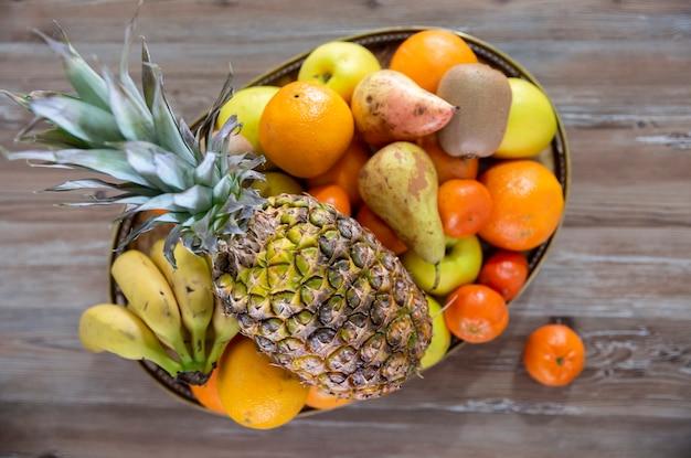 Bovenaanzicht van gemengd fruit in mand op oude houten bord. concept van voedsel, fitness en gezondheid.