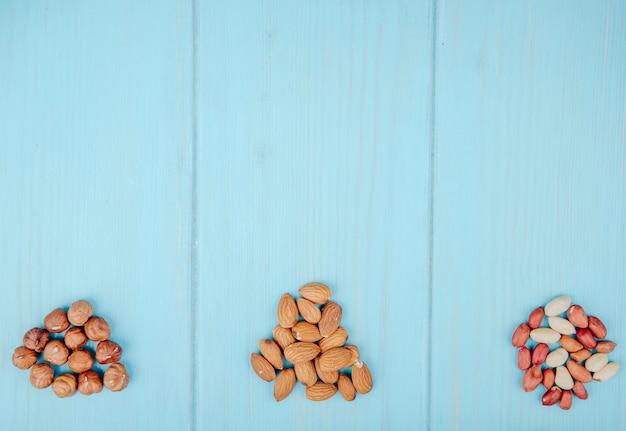 Bovenaanzicht van gemengd van noten hoop geïsoleerd op blauwe achtergrond amandelen hazelnoten en pinda's met kopie ruimte