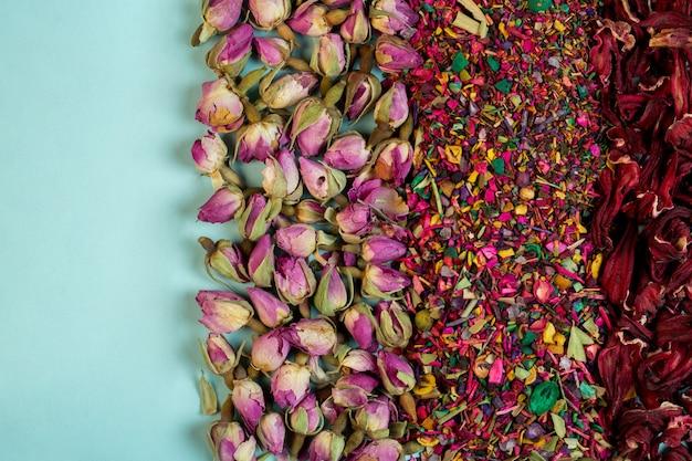 Bovenaanzicht van gemengde kruidenthee bloeit rozenblaadjes gedroogde rozenknoppen en kruiden op blauw