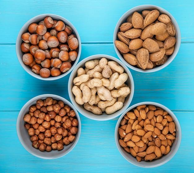 Bovenaanzicht van gemengde noten in de schaal en zonder schaal in kommen amandel hazelnoten en pinda's op blauwe achtergrond
