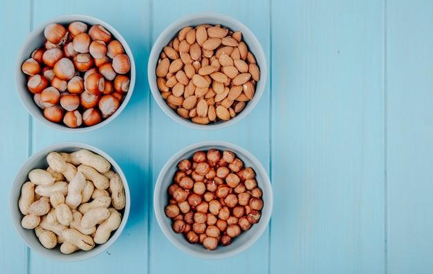 Bovenaanzicht van gemengde noten in schaal en zonder schaal in kommen amandel-hazelnoten en pinda's op blauwe achtergrond met kopie ruimte