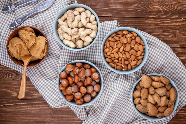 Bovenaanzicht van gemengde nutsin schelpen in kommen pinda's hazelnoten amandelen op geruite tafellaken