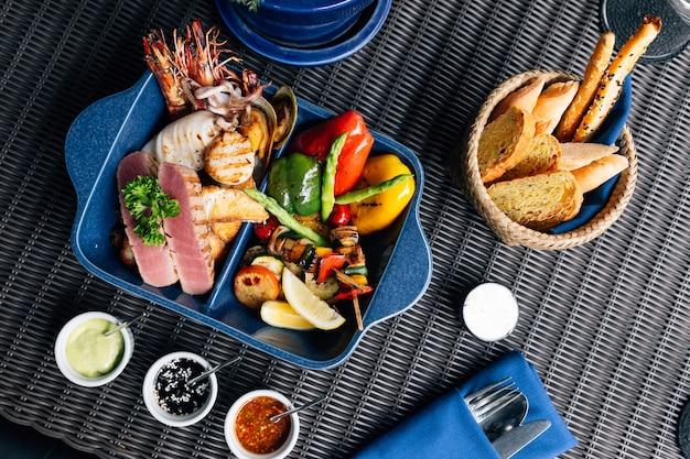 Bovenaanzicht van gemixte zeevruchten, gegrild zoals vis, inktvis, garnalen, mosselen en groenten.