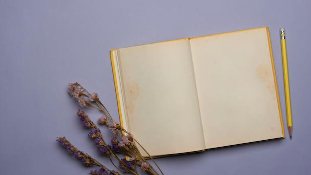 Bovenaanzicht van geopende notebook, potlood en gedroogde bloem op paarse achtergrond
