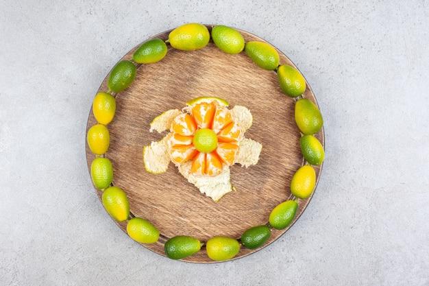 Bovenaanzicht van gepelde mandarijn met stapel kumquats op houten bord.