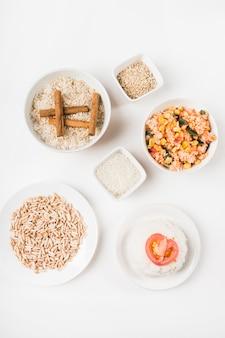 Bovenaanzicht van gepofte rijst; chinese gefrituurde rijst en ongekookte rijst met kaneelstokjes