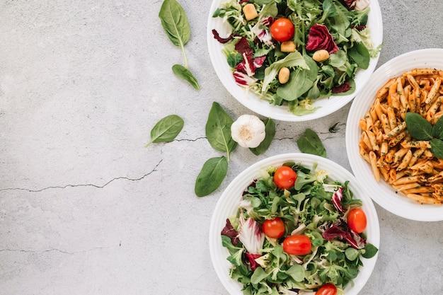 Bovenaanzicht van gerechten met salades en knoflook met kopie ruimte
