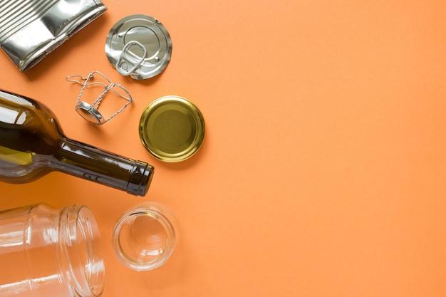 Bovenaanzicht van gerecycled glas en metaal op oranje met kopie ruimte