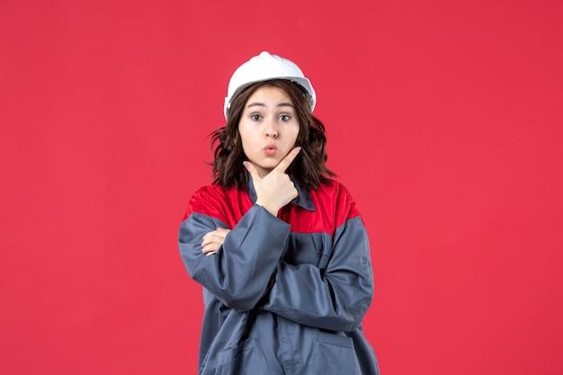 Bovenaanzicht van gerichte vrouwelijke bouwer in uniform met helm en geconcentreerd op iets op geïsoleerde rode achtergrond