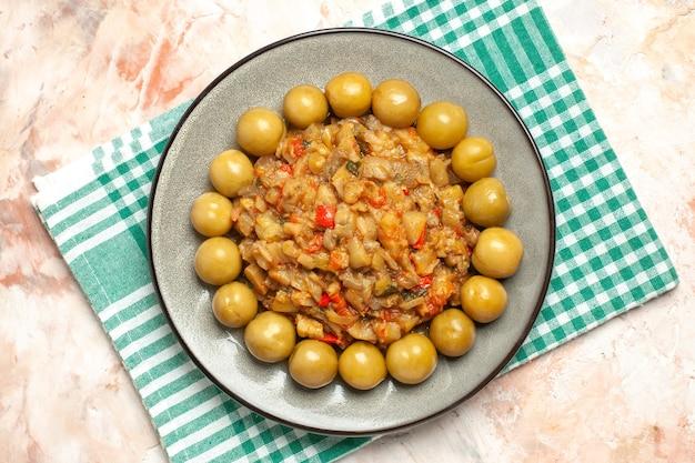 Bovenaanzicht van geroosterde auberginesalade en ingelegde pruimen op ovale plaat op turkoois wit geruit oppervlak