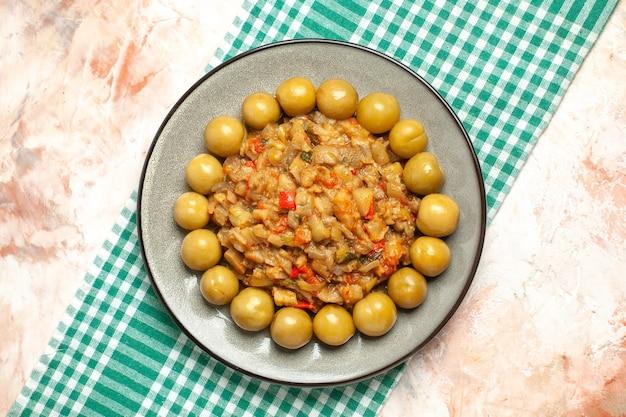 Bovenaanzicht van geroosterde auberginesalade en ingelegde pruimen op plaat op turkoois wit geruit oppervlak