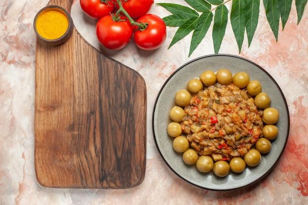 Bovenaanzicht van geroosterde auberginesalade op plaat op snijplank tomaten op naakt oppervlak