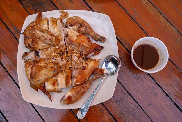 Bovenaanzicht van geroosterde kip kruiden met gebakken knoflook met pittige zoetzure saus op tafel