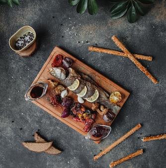 Bovenaanzicht van geroosterde vis met citroen groenten en narsharab granaatappelsaus op een houten bord op donkere muur