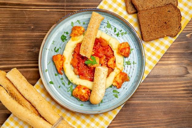 Bovenaanzicht van gesauteerd vlees met aardappelpuree en broden op bruin houten tafel
