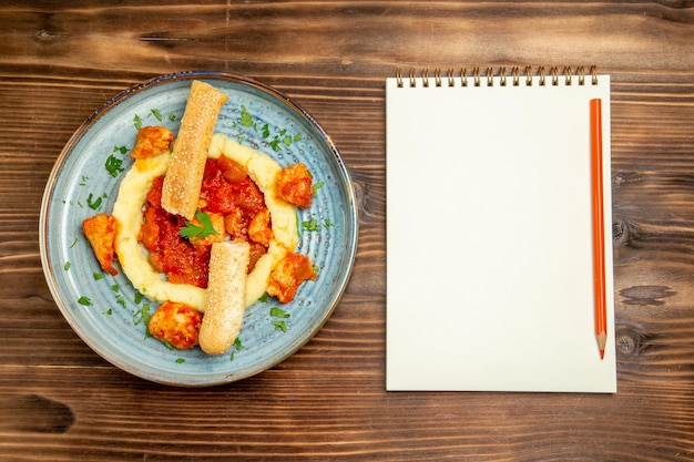 Bovenaanzicht van gesauteerd vlees met aardappelpuree en gesneden broodje op bruin houten tafel