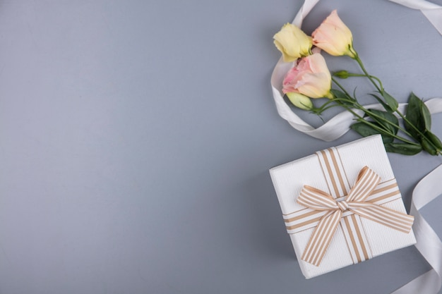 Bovenaanzicht van geschenkdoos en bloemen met lint op grijze achtergrond met kopie ruimte