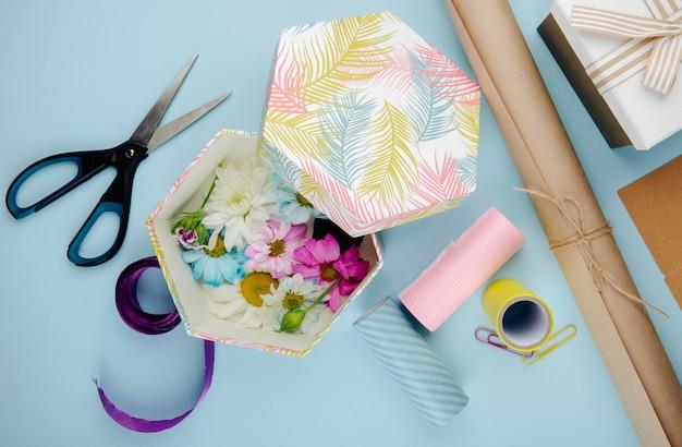Bovenaanzicht van geschenkdoos gevuld met kleurrijke chrysanthemum bloemen met madeliefje en schaar rollen papier en paperclips op blauwe achtergrond