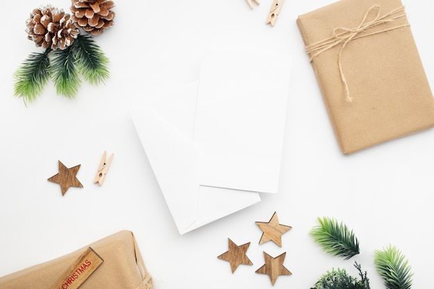 Bovenaanzicht van geschenkdoos, lint, fir takken, kegels, anijs op witte tafel