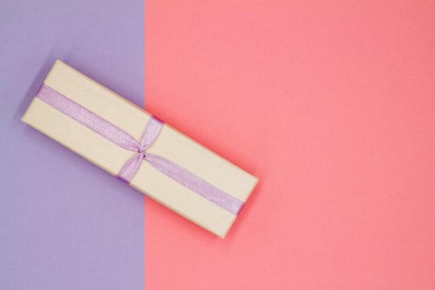 Bovenaanzicht van geschenkdoos met paars lint op een gekleurde achtergrond