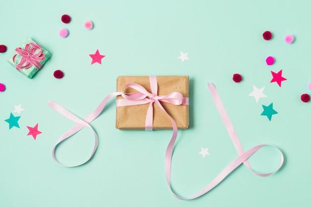 Bovenaanzicht van geschenkdoos met pom-poms en sterren
