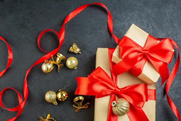 Bovenaanzicht van geschenkdoos met rood lint en decoratie accessoires op donkere achtergrond