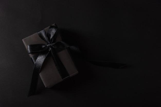 Bovenaanzicht van geschenkdoos verpakt in zwart papier en zwart striklint