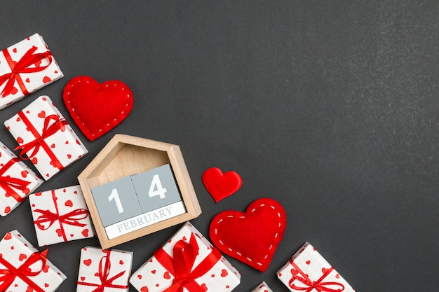 Bovenaanzicht van geschenkdozen, houten kalender en rode textiel harten op kleurrijke achtergrond. de veertiende februari. st valentijnsdag concept met kopie ruimte