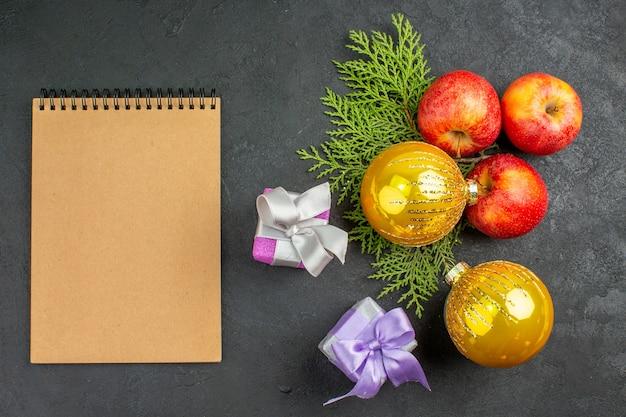 Bovenaanzicht van geschenken en natuurlijke biologische verse appels, decoratieaccessoires en notitieboekjes op zwarte tafel