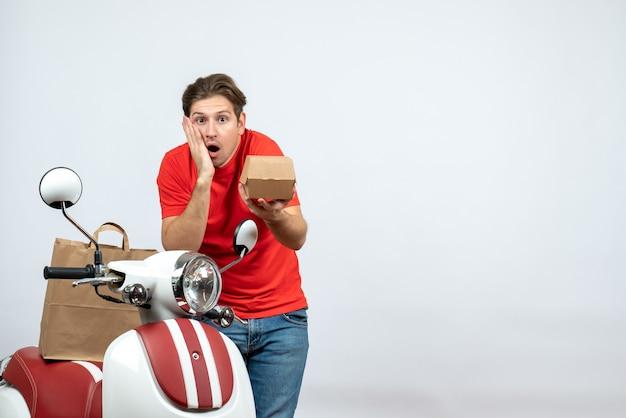 Bovenaanzicht van geschokt emotionele bezorger in rood uniform staande in de buurt van scooter met bestellingen op witte achtergrond