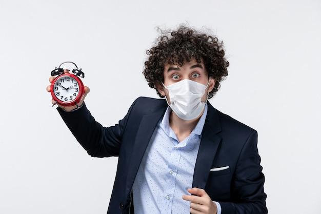 Bovenaanzicht van geschokt verrast zakenman in pak en het dragen van zijn masker met klok holding