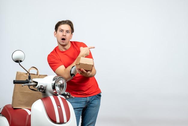 Bovenaanzicht van geschokte bezorger in rood uniform staande in de buurt van scooter die bestelling wijst terug op witte achtergrond