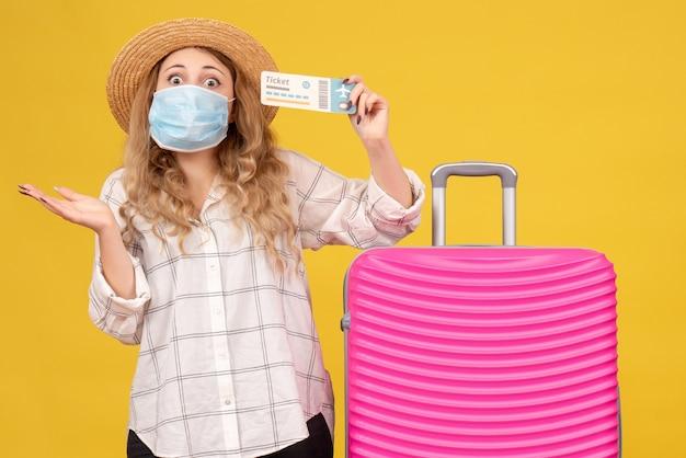 Bovenaanzicht van geschokte jonge dame die masker draagt dat kaartje toont en zich dichtbij haar roze tas bevindt
