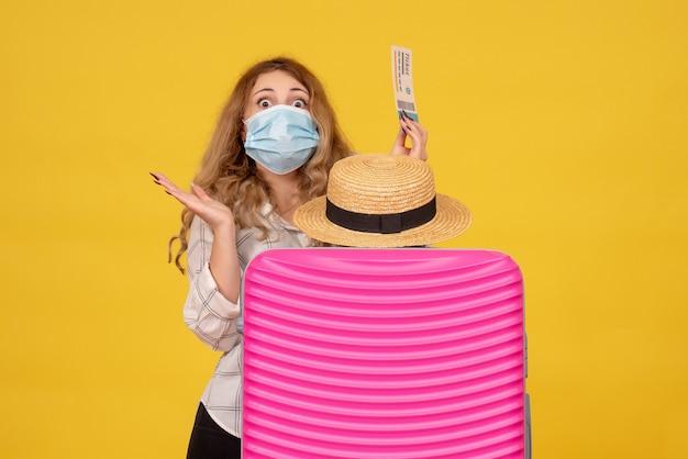Bovenaanzicht van geschokte jonge dame die masker draagt met kaartje en achter haar roze tas staat