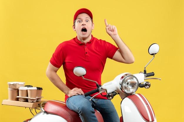Bovenaanzicht van geschokte jonge kerel die rode blouse en hoed draagt die bevelen levert die op gele achtergrond benadrukt