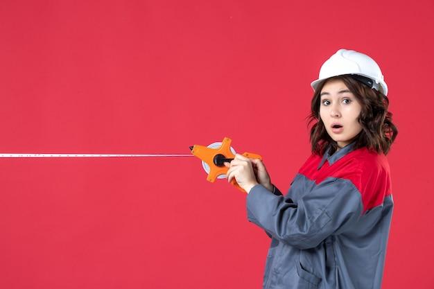 Bovenaanzicht van geschokte vrouwelijke architect in uniform met veiligheidshelm die meetlint opent op geïsoleerde rode achtergrond