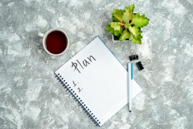 Bovenaanzicht van geschreven spiraalvormig notitieboekje en bloempot een kopje thee op grijze achtergrond