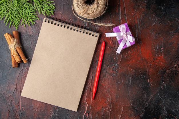 Bovenaanzicht van gesloten notitieboekje kaneellimoenen en cadeau op donkere achtergrond