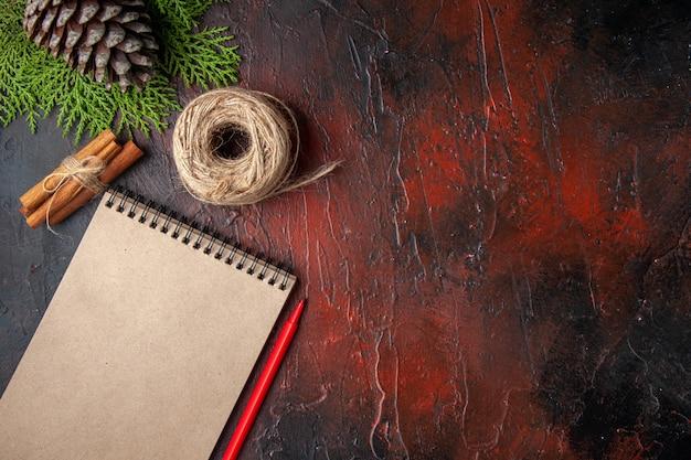 Bovenaanzicht van gesloten notitieboekje met pen kaneel limoenen een bal van touw op donkere achtergrond
