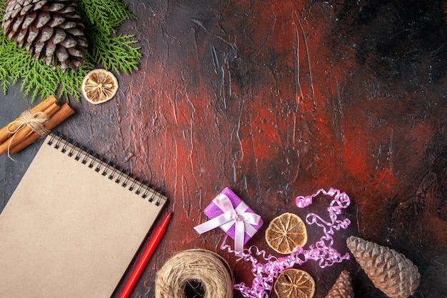 Bovenaanzicht van gesloten notitieboekje met pen, kaneellimoenen en een bal touw op donkere achtergrond