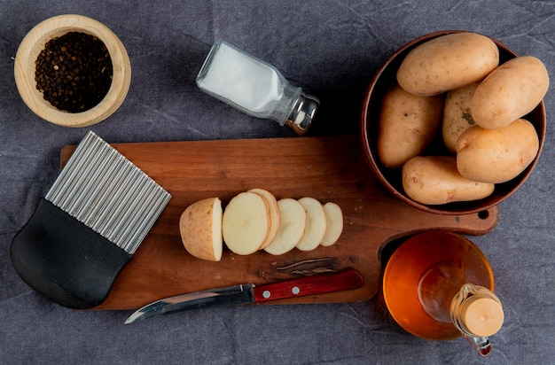 Bovenaanzicht van gesneden aardappel en mes met chips cutter op snijplank met andere in kom zout zwarte peper boter op grijze doek