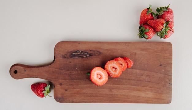 Bovenaanzicht van gesneden aardbeien op een houten snijplank op wit