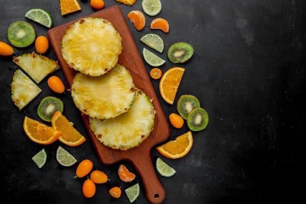 Bovenaanzicht van gesneden ananas op snijplank met andere citrusvruchten rond op zwarte ondergrond