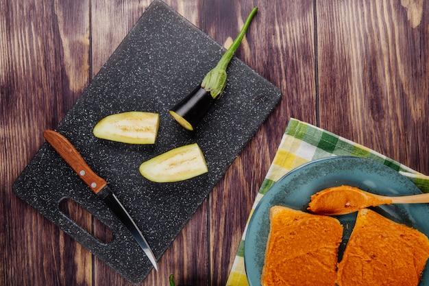 Bovenaanzicht van gesneden aubergine en keukenmes aan boord voor het koken en toast met auberginekaviaar