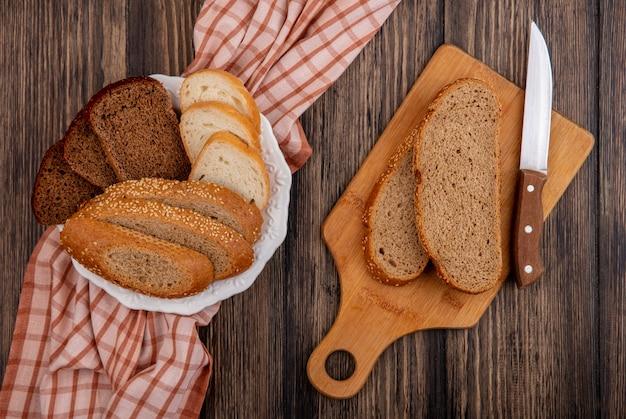 Bovenaanzicht van gesneden brood als gezaaide bruine cob rogge en witte in plaat op geruite doek en op snijplank met mes op houten achtergrond